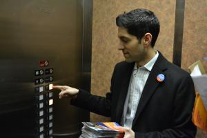 Akash Khokhar presses the elevator buttons in a downtown apartment building