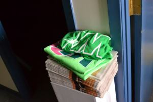Two green Wildrose T-shirts sit on top of a stack of Edmonton Senior papers.