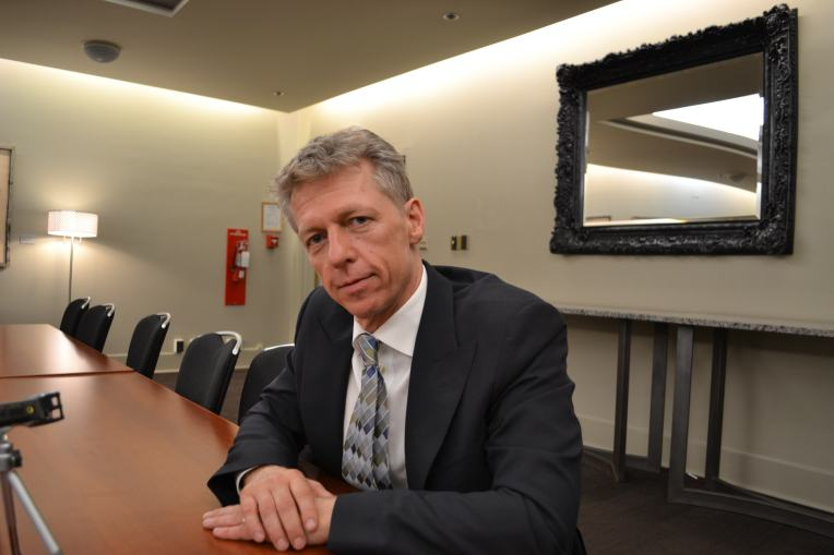 James Orbinski looks into the camera at a conference table in the Jubilee Auditorium