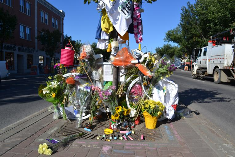 A white painted bicycle has been placed in a median on Whyte Ave. It is covered in flowers and cards for Isaak. A truck passes to the right.