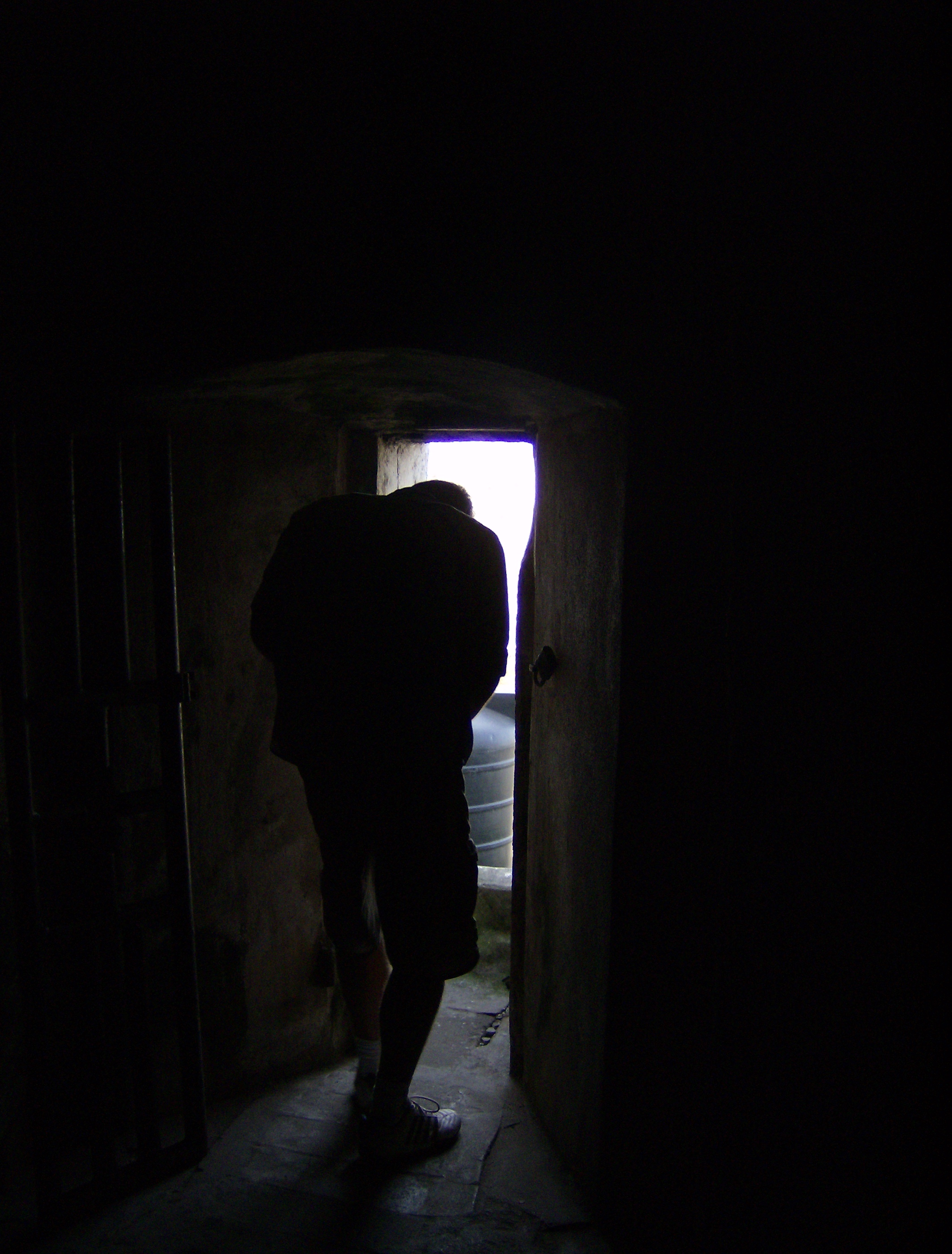 Dark room with light through door - A Man Crouches To Squeeze Through A Doorway Out Of A Dark Room And Into The