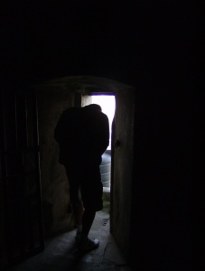 A man crouches to squeeze through a doorway out of a dark room and into the light.