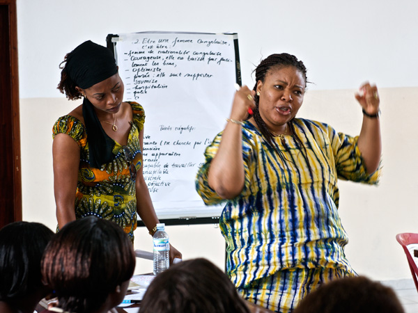 Nobel Peace Prize winner Leymah Gbowee stands in front of a white board with her hands raised like she's trying to push the crowd into action.