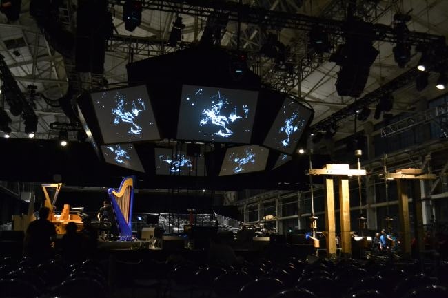 A circle of screens showing constellations hang above the instruments on stage at the Craneway Pavillion