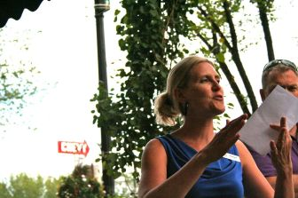 Jill raises her hands in front of a tree-lined Whyte Avenue backdrop.