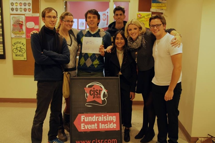 A group of radio hoodlums hug around a sign with the fundraising total from their FunDrive show. No windows are present, because CJSR is forever cursed to live in the basement.